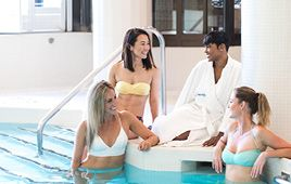 A group lounges by the pool between spa services at Elmwood Spa
